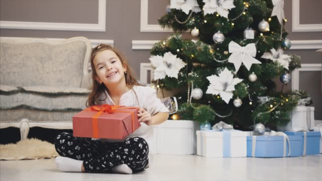 Advertising video where little girl got a giftbox and presents it in front of the camera on Christmas background.