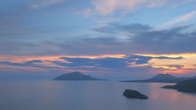 Aegean Sea on sunset, Greece Sunset over island in Aegean Sea, as viewed from cape Sounion. With horizontal camera pan sounion stock videos & royalty-free footage
