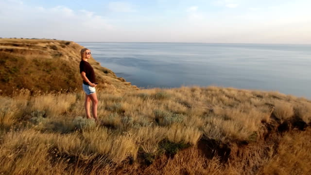 Aerial 360 degree shot of a courageous woman standing on a sea cliff at sunset video