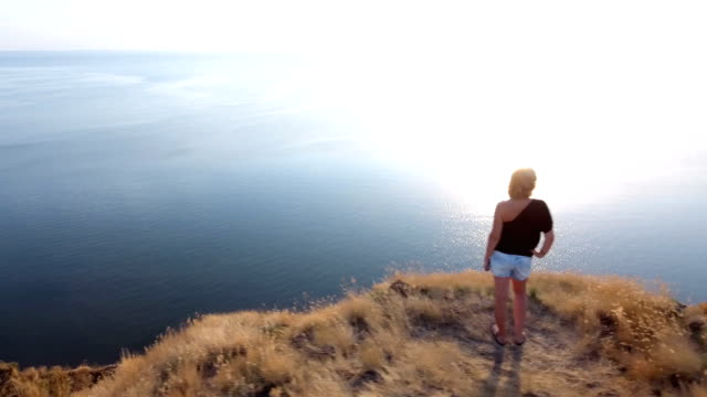 Aerial 360 degree shot of a stylish woman standing on a seacoast cliff at sunset video