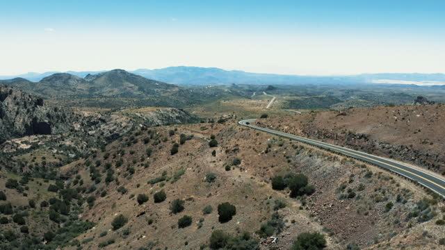 Aerial 4k drone footage of mountain pass with cars on a bright sunny day with blue sky in Gila National Forest crossing state line between New Mexico and Arizona in the United States