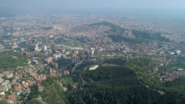 aerial 4k footage from drone of tibidabo in barcelona, spain. panoramic city view. mountain roads and buildings. clear sky sunny day. - jesus christ filmów i materiałów b-roll