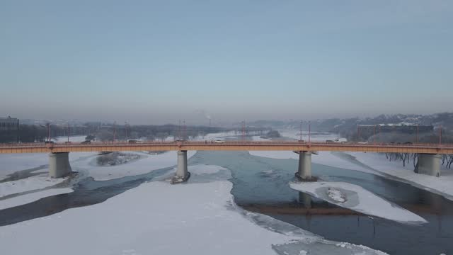Aerial 4K footage of a flight over an icy river and bridge in front in Kaunas, Lithuania