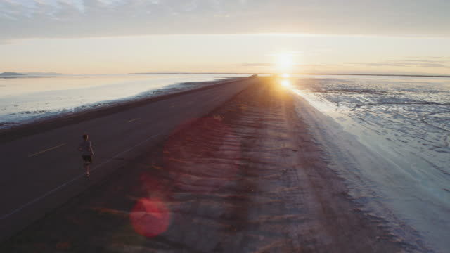 Aerial 4K: Running Toward the Sun Aerial view of a young woman on a sunrise run at the Bonneville Salt Flats individuality stock videos & royalty-free footage