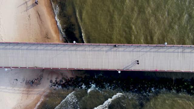 aerial 4k top-view-video der brücke zum meer von der küste zum meer führt - litauen stock-videos und b-roll-filmmaterial