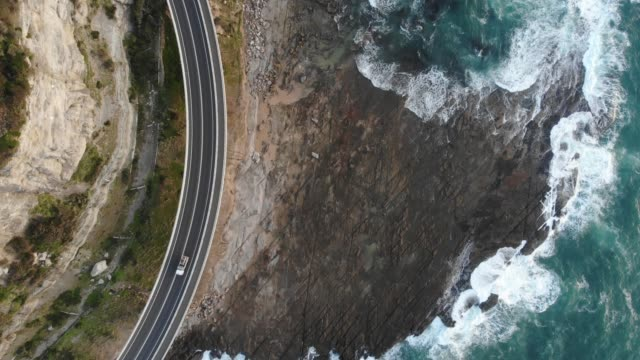 Aerial 4K Video Above of Highway Along Ocean Coast in NSW Australia Drone shot looking down on road curving along rocky sea coast with waves crashing onto shore. Cars are driving along highway. coastal feature stock videos & royalty-free footage