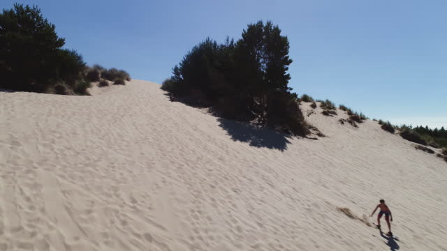 Aerial 4K video of people sand boarding down sand dunes while on vacation