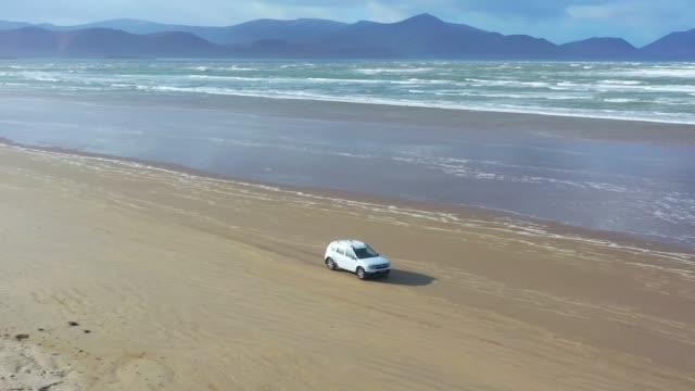 美しいビーチでの車の運転の空中4k ビュー。アイルランドのインチビーチでの suv 運転 - 陸の乗り物点の映像素材/bロール