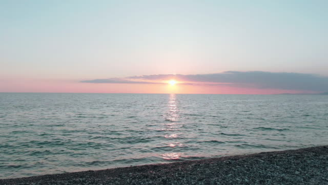 vídeos de stock e filmes b-roll de aerial 4k view. stunning sunset sun over the sea. beautiful cinematic scene. golden sun sets over the horizon, flying above the surface of the water - linha do horizonte sobre água