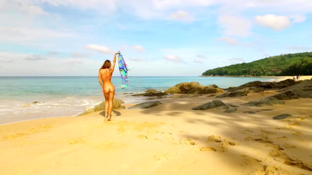 aerial: a girl posing and dancing on the beach. - phuket video stock e b–roll