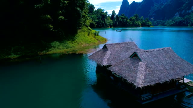 Aerial: A house with a thatched roof on the lake and a boat sailing alongside. video