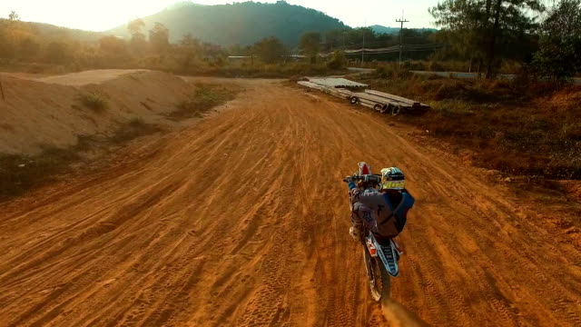 Aerial: A man rides a bike on the rear wheel. video