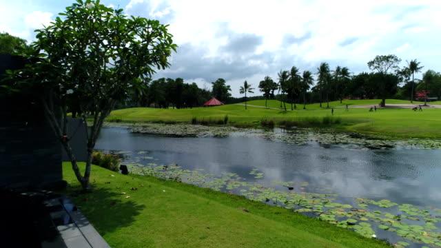 vídeos y material grabado en eventos de stock de antena: una vista de golf y un pequeño lago de una villa de la piscina. - charca
