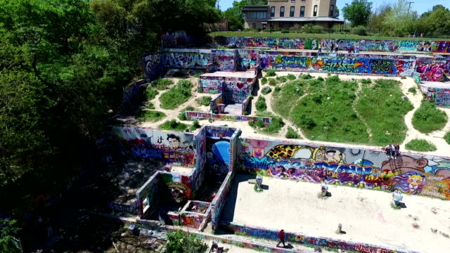 Aerial Above Austin Texas Hill Country looking down at the Castle Hill Graffiti wall with Hills , castle , and outdoor public graffiti wall in view in the air over ATX 2016 drone view close view video