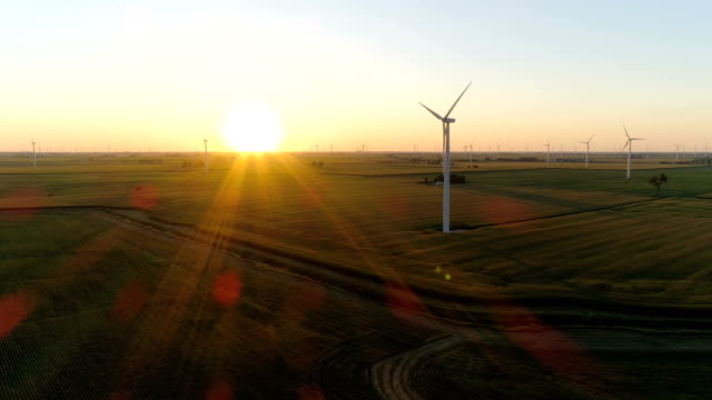 Aerial above countryside field and wind turbine into sunset with light beams