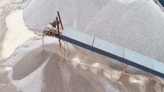 Aerial above view of Conveyors is rolling and dropping off gravels