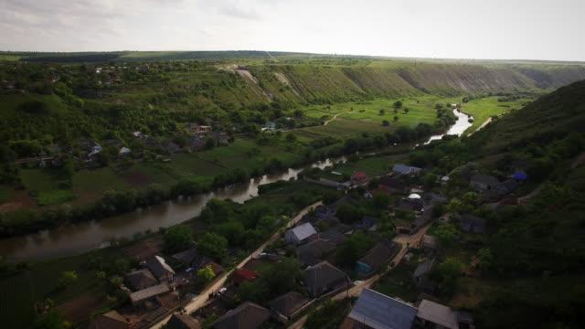 4k aerial above village and river in moldova on sunset - молдавия стоковые видео и кадры b-roll