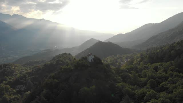 stockvideo's en b-roll-footage met antenne: antenne: vliegen over kapel neergestreken op de bergtop - klooster