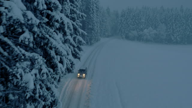 Aerial All terrain vehicle on snowbound forest road at night video