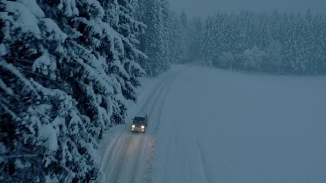 Vehículo de todo terreno vista aérea snowbound forest road por la noche - vídeo