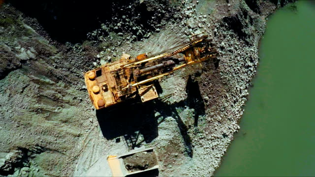 Aerial. An excavator is extracting minerals in an open pit video