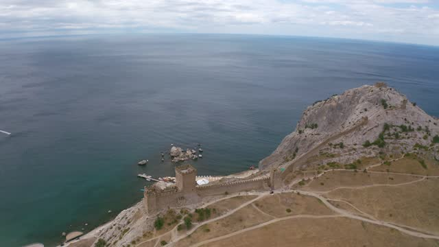 Aerial around landscape Genoese fortress on mountain top, Black Sea shore and Sudak city. Ancient fortress on modern resort city architecture background from flying drone. Point of interest