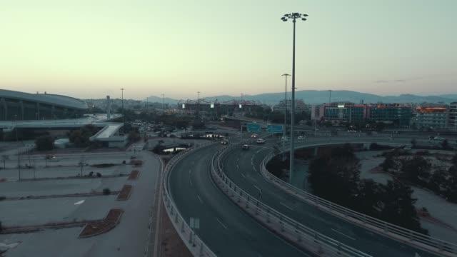 stockvideo's en b-roll-footage met luchtfoto - athene - piraeus - pireas, griekenland, vliegen boven een verkeersknooppunt, bruggen, tram, kabelbaan en auto's bij zonsondergang - athens