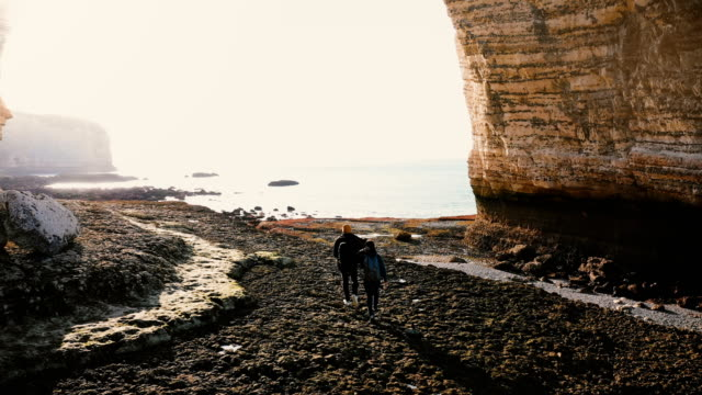 Aerial back view of happy tourist man and woman walking along amazing pebble beach under epic giant rock arch Normandy. Aerial back view of happy tourist man and woman walking along amazing pebble beach under epic giant rock arch Normandy. Young traveler couple exploring unreal coral cliff low tide shore at Etretat. normandy stock videos & royalty-free footage