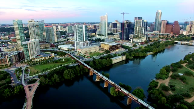 Aerial: Backing away from Austin Texas Downtown Over Town Lake with City Lights on Ready for Nightlife Aerial: Backing away from Austin Texas Downtown Over Town Lake with City Lights on Ready for Nightlife as the sun sets behind the Texas Hill Country the Cityscape lights up with lights post modern architecture stock videos & royalty-free footage