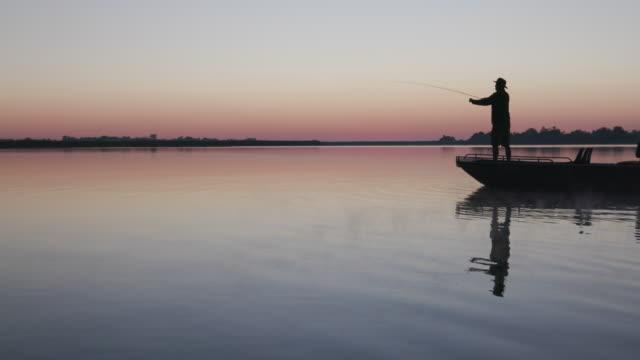 z podświetlenia lotniczego widok rybaka latać połowów z łodzi - podświetlony filmów i materiałów b-roll
