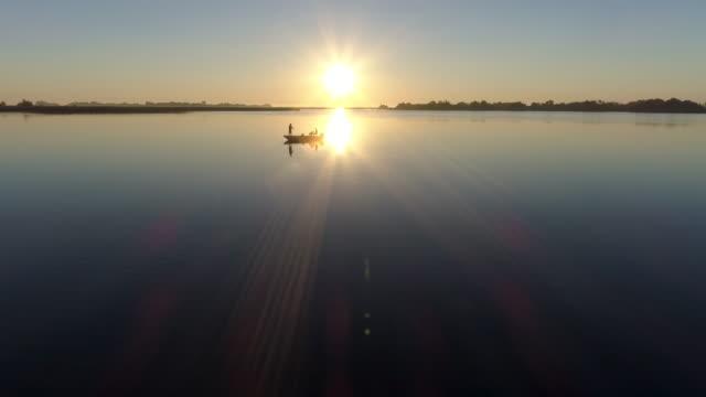 aerial hintergrundbeleuchtung ansicht von fischer fliegenfischen vom boot aus - fang stock-videos und b-roll-filmmaterial