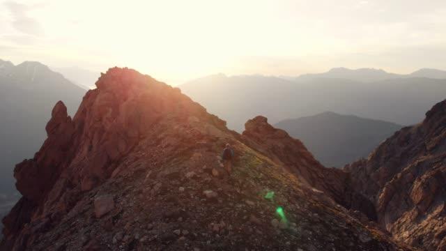 aerial: backpacker hiking to the mountain top in backlight, slow motion - ekoturystyka filmów i materiałów b-roll