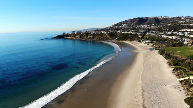 vídeos de stock e filmes b-roll de aerial beach view drone shot flying from the sandy shore, and grass to the crystal clear water and cliffs at salt creek beach in laguna, orange county, california. - califórnia