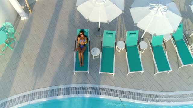 Aerial: Beautiful girl lies on a sunbed by the pool, drinking a cocktail. Aerial: Beautiful girl in bikini lies on a turquoise color sunbed with a sun umbrella and sunbathng by the pool and drinks a cocktail. military private stock videos & royalty-free footage