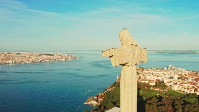 Aerial bird view around Sanctuary of Christ the King, Santuario de Cristo Rei in Lisbon, Portugal. Drone footage at sunset. Catholic monument