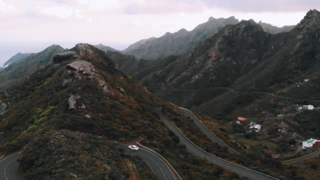 vidéos et rushes de vue aérienne d'oiseau - voitures conduisant au-dessus du col de montagne dans le parc national anaga, tenerife - abaisser