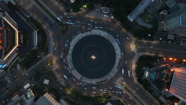 stockvideo's en b-roll-footage met aerial birds eye overhead top down roterende weergave van drukke stadsverkeer in de selamat datang monument rotonde 's nachts - bovenkleding