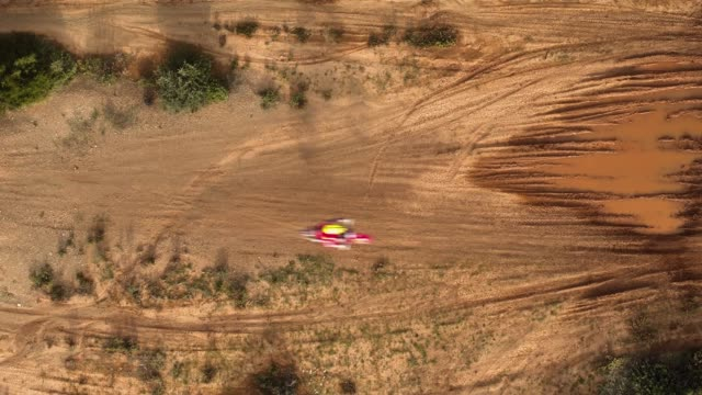 Aerial, bird's eye view, motocross sports and practice at the forest, 2 motocross athletes landing with their motorbikes after a high jump video