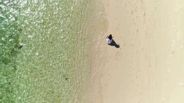 Aerial: Brunette girl in a white dress is runing along the beach by the water. video