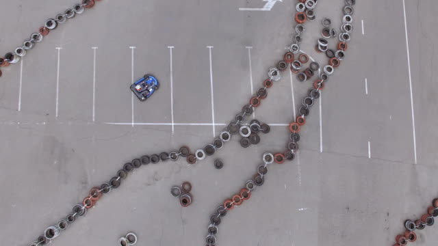Aerial camera flying upwards revealing carts on racing track