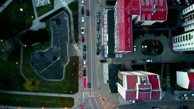 Aerial camera following biker in blue riding his cycle along bicycle paths, top view. Modern urban residential area. FullHD video video