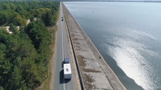 Aerial. Camper van recreational vehicle trailer on dam. 4k.
