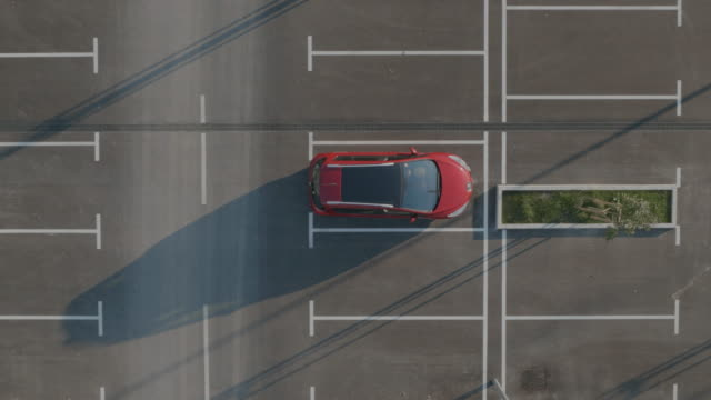 4K Aerial: Car Departs from Empty Parking Lot video