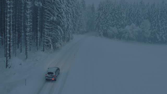vidéos et rushes de voiture aérienne conduisant le long d'une route de forêt enneigée la nuit - blizzard