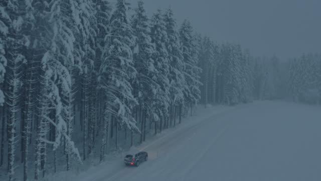 stockvideo's en b-roll-footage met luchtfoto auto rijden langs sneeuw bedekte bos weg bij nacht - mist donker auto