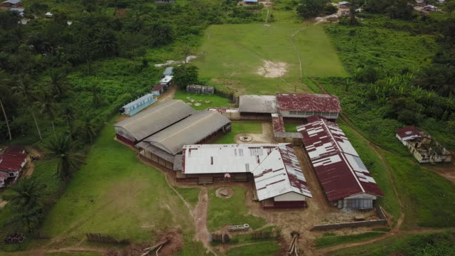 aerial circling around third world school with liberian or us flag on pole - liberia video stock e b–roll