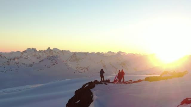 antenn kretsande drönare skott av en grupp skidåkare på kanten av ett snöigt berg vid solnedgången - vintersport bildbanksvideor och videomaterial från bakom kulisserna