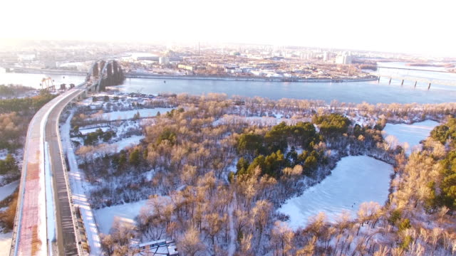 4K Aerial. City urban landscape with Unfinished highway, buildings, frozen river  and bridge