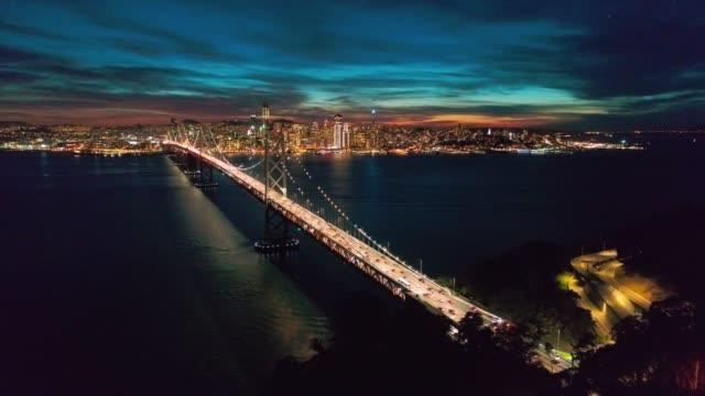vídeos y material grabado en eventos de stock de video flythrough de paisaje aéreo del puente de la bahía y san francisco skyline por la noche - san francisco