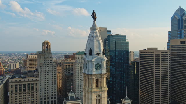 Aerial close view on Philadelphia City Hall with the William Penn statue atop of the tower in front of Downtown District, Philadelphia, Pennsylvania.  Drone video with the panning camera motion.